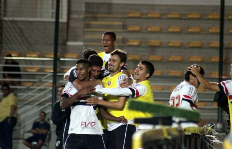 Gabriel Novaes é abraçado pelos companheiros após o gol da classificação (Foto: Fernando Martinez/Aguante)