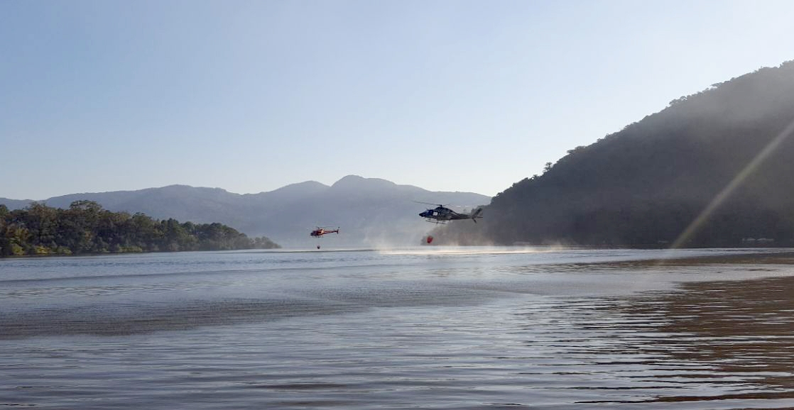 Os helicópteros Arcanjo 01, dos Bombeiros, e Águia 02, da PM, trabalharam lado a lado no combate às chamas - PM/Divulgação/ND