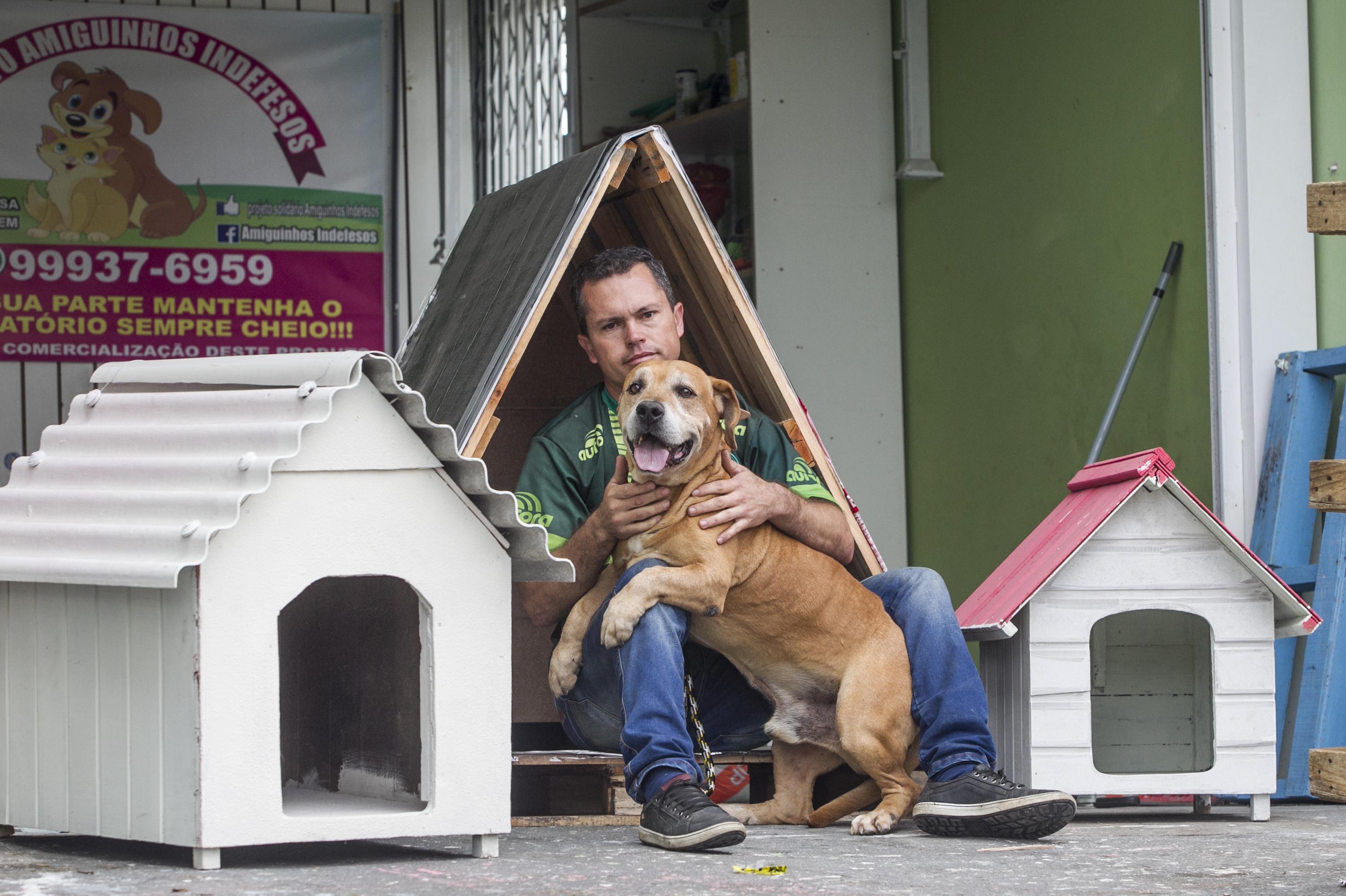 Ezequiel Nunes com Duke, um dos seus cães oficiais, e as casinhas que ele faz para os cachorros sem donos - Marco Santiago/ND