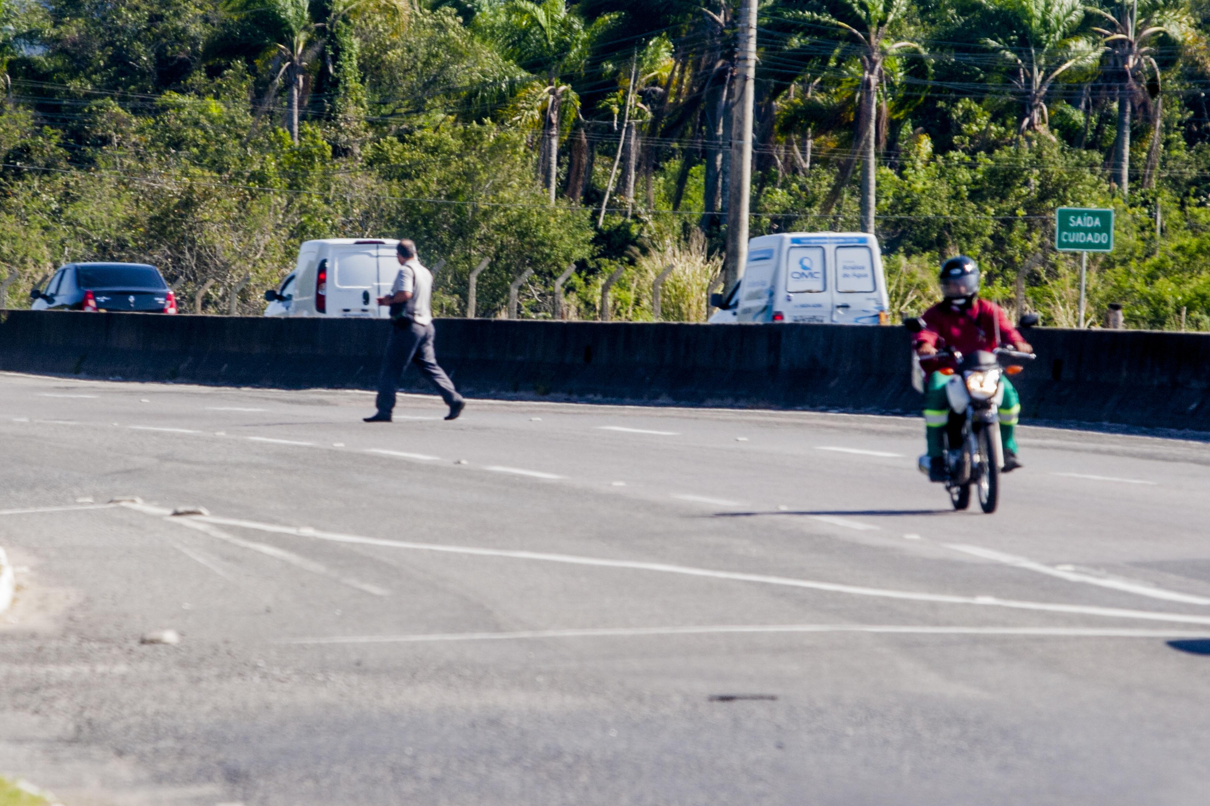 Pedestre pula a mureta que separa as pistas da SC-401 e atravessa a rodovia em meio aos veículos - Flávio Tin/ND
