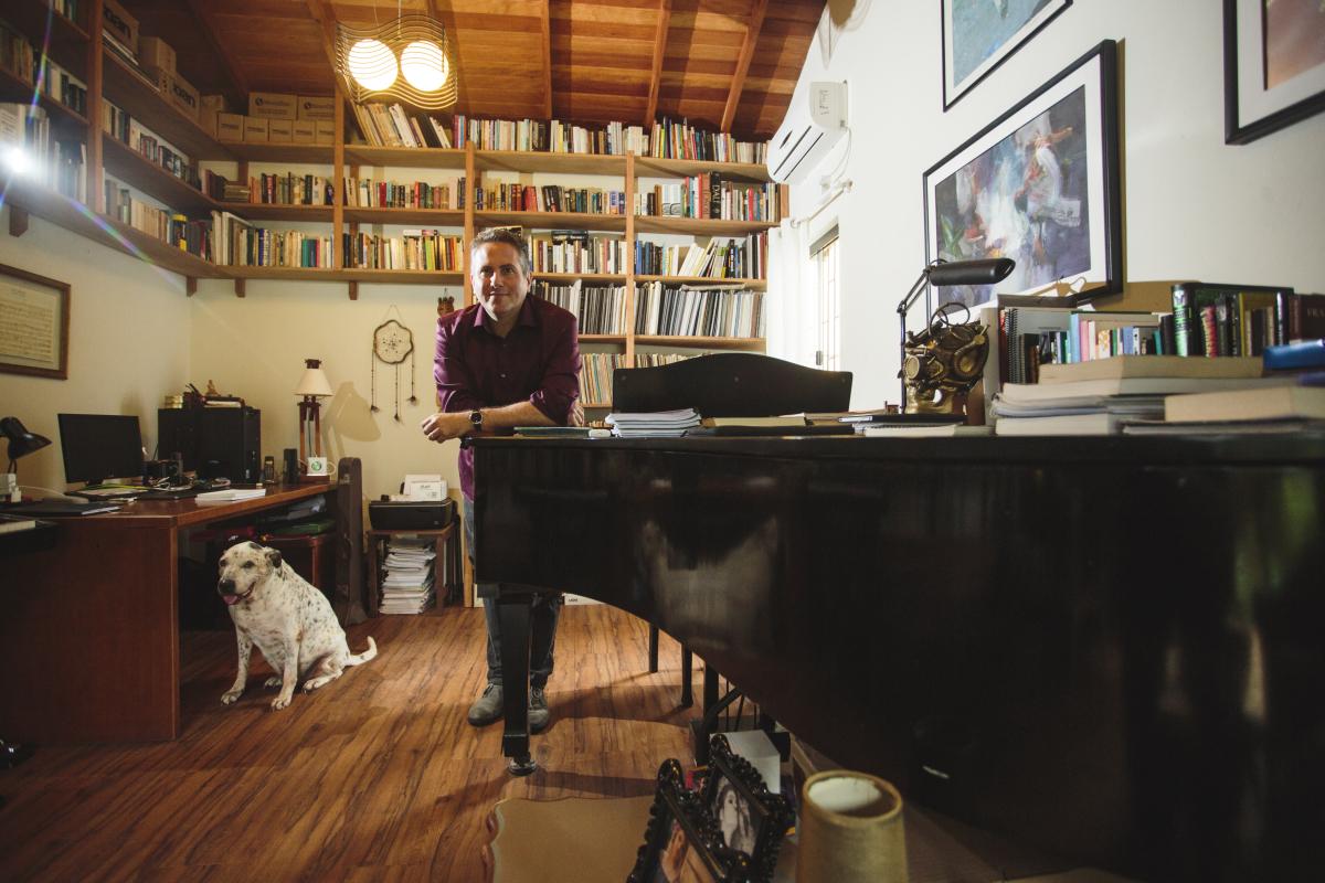 Alberto Heller em seu estúdio, na companhia de um de seus cachorros, piano e livros - Daniel Queiroz/ND