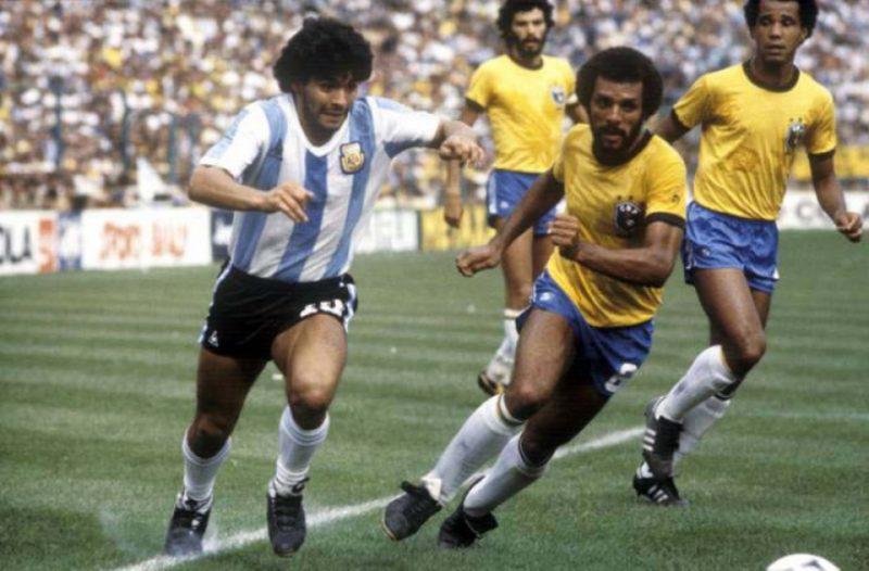 Rivalidade eterna. Na Copa de 1982 o Brasil levou a melhor: 3 x1. Maradona recebe a marcação do lateral Júnior, sendo observado pelo zagueiro Luisinho. Sócrates observa o lance. – Foto: (Foto: Divulgação)