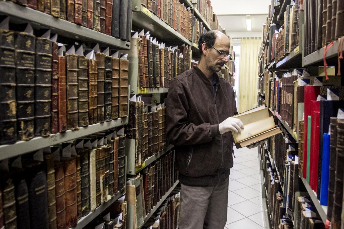 Bibliotecário Alzemi Machado e um dos volumes do Auto da Devassa - Marco Santiago/ND