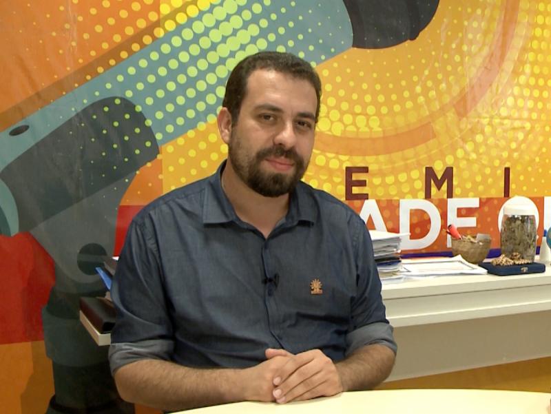 Guilherme Boulos sentado em uma mesa