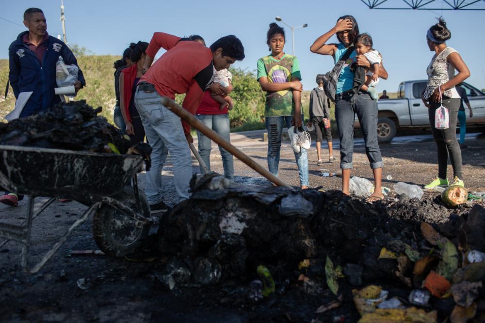 Venezuelanos observam os restos de suas roupas, alimentos e objetos que foram queimadas por moradores de Pacaraima - Avener Prado/Folhapress