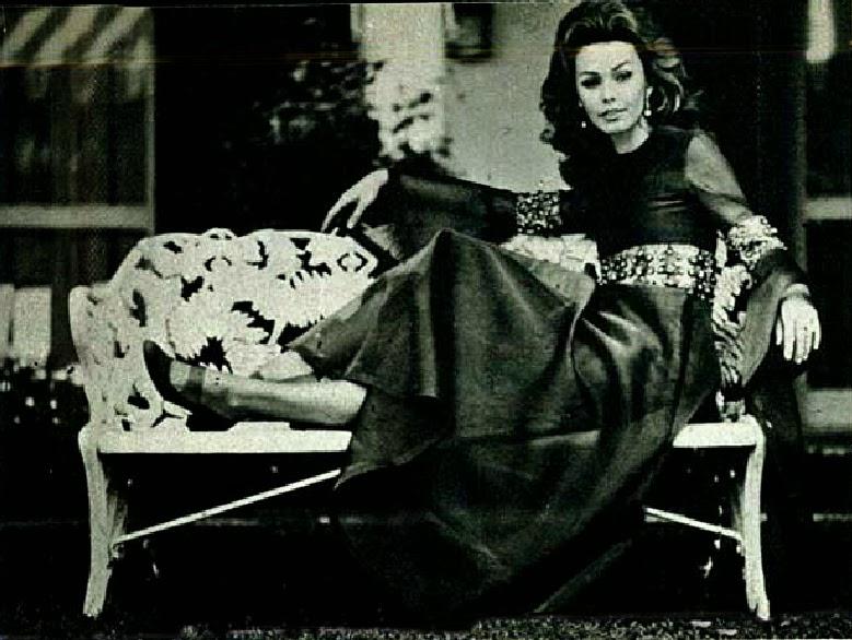 Foto da atriz Ângela Diniz, foto em preto e branco de uma mulher com vestido preto sentada em uma banco de ferro branco. Fim da descrição