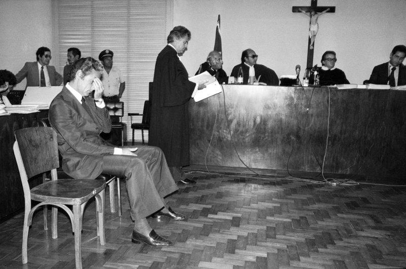 Foto do julgamento de Doca Street, assassino de Ângela Diniz. Imagem com Doca sentado à esquerda e outros homens em pé atrás. Fim da descrição