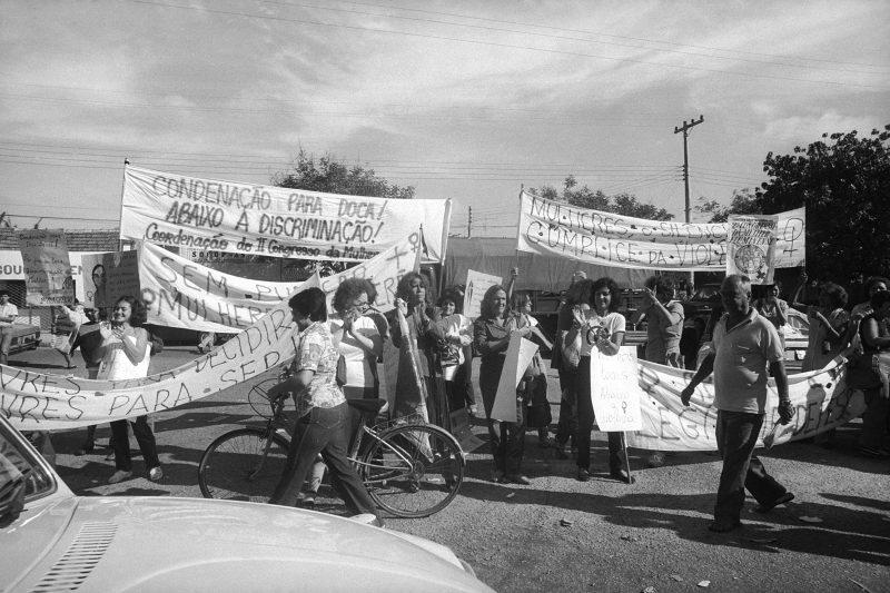 Foto em preto e branco de manifestação com mulheres e segurando cartazes pedindo a condenação de Doca Street. Fim da descrição