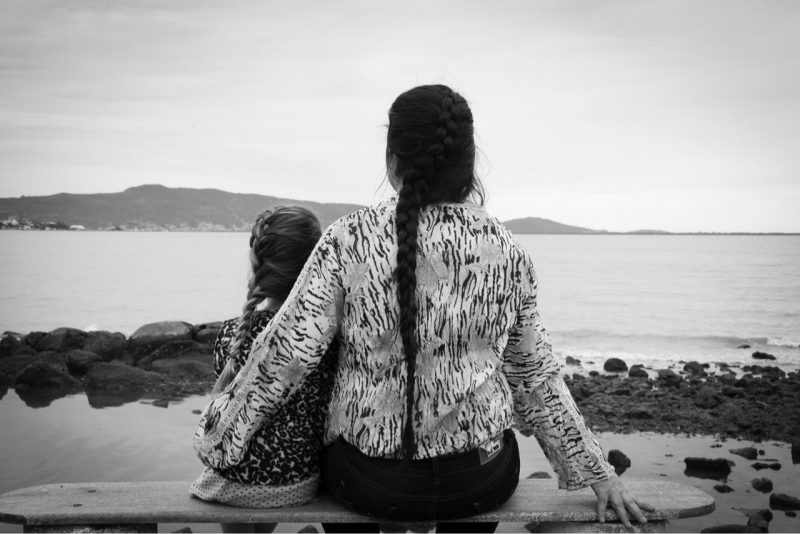 Foto de mãe e filha sentadas em um banco de frente pro mar. Fim da descrição