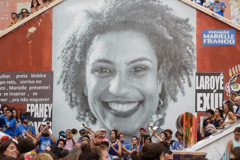 Imagem de uma escadaria com a foto de Marielle Franco com várias pessoas em volta. Fim da descrição.