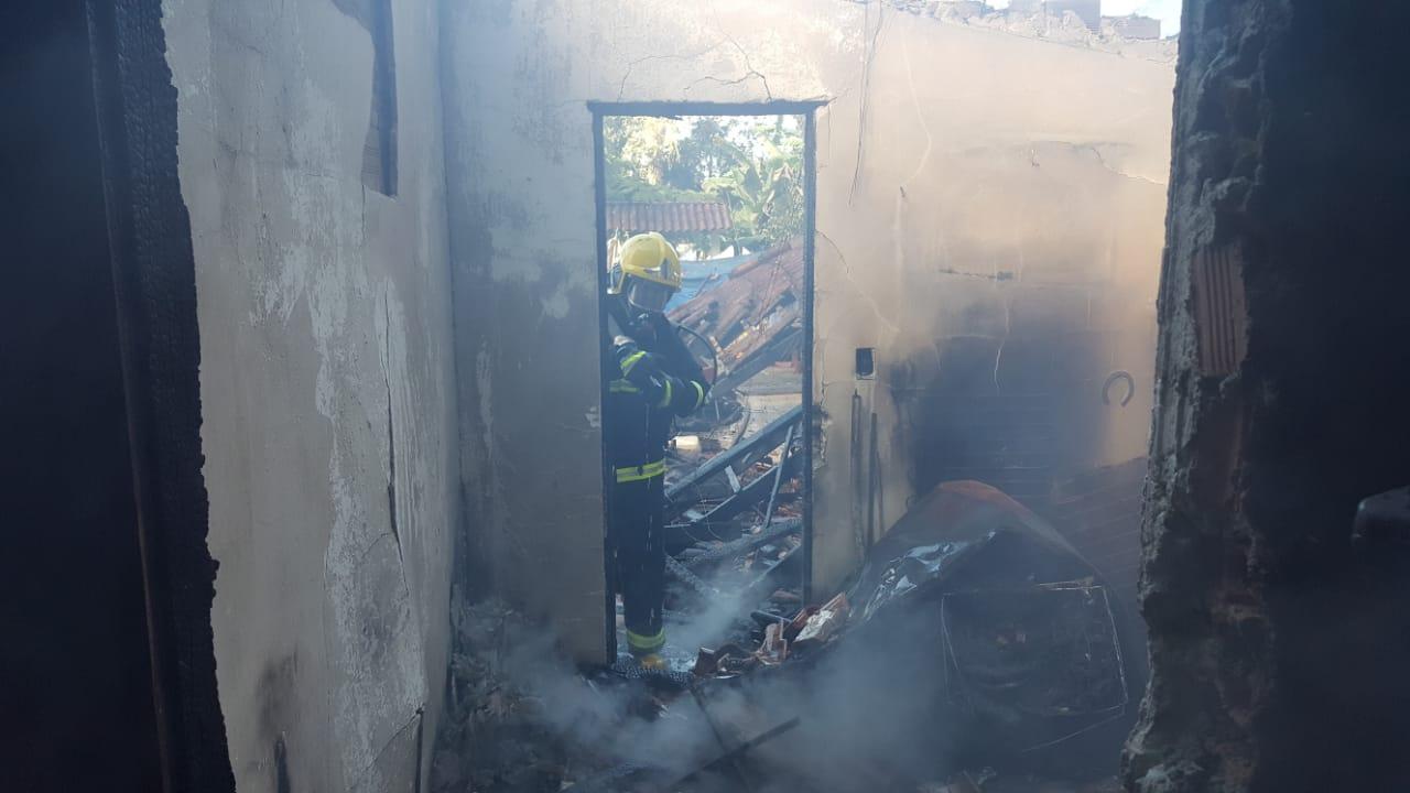 Bombeiro durante ação de rescaldo na casa queimada - Corpo de Bombeiros Militar de Itapoá/Divulgação/ND