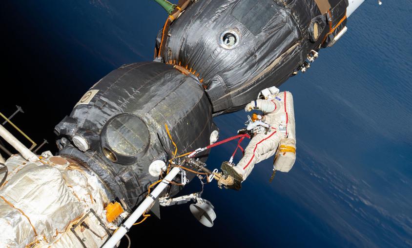O astronauta russo Oleg Kononenko (terno com listras vermelhas) trabalha fora da Estação Espacial Internacional, a mais de 400 quilômetros da Terra, para inspecionar a espaçonave Soyuz MS-09 - (NASA)/33Giga/ND