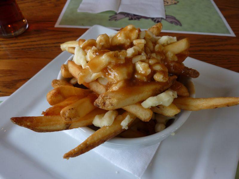 No Canadá, a batata frita é servida de forma diferente: coberta com queijo e caldo de carne. O prato típico é conhecido como poutine - Foto: Divulgação - Foto: Divulgação/Rota de Férias/ND