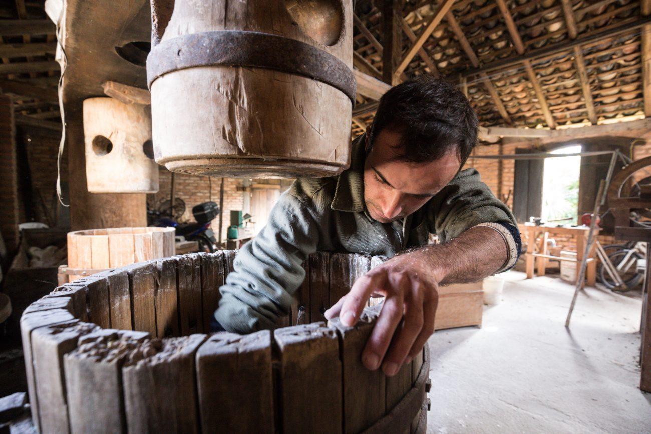 João José Heidenreich coloca a massa crua de mandioca na barrica para ser prensada pelo fuso - Moinho de farinha ribeirão da Ilha_Anderson Coelho_1155