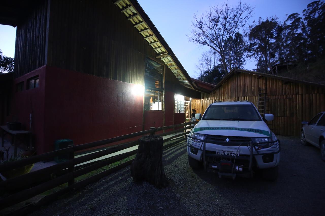 Viatura do Instituto Geral de Perícia na casa onde os três corpos foram encontrados, em Alfredo Wágner - Anderson Coelho/ND
