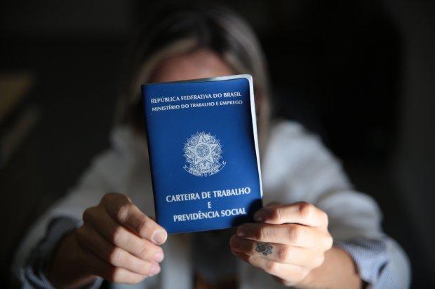 mulher mostrando a carteira de trabalho
