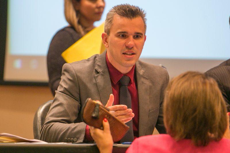 Douglas Borba usa um blazer cinca e camisa cor vinho. Ele gesticula em uma conversa