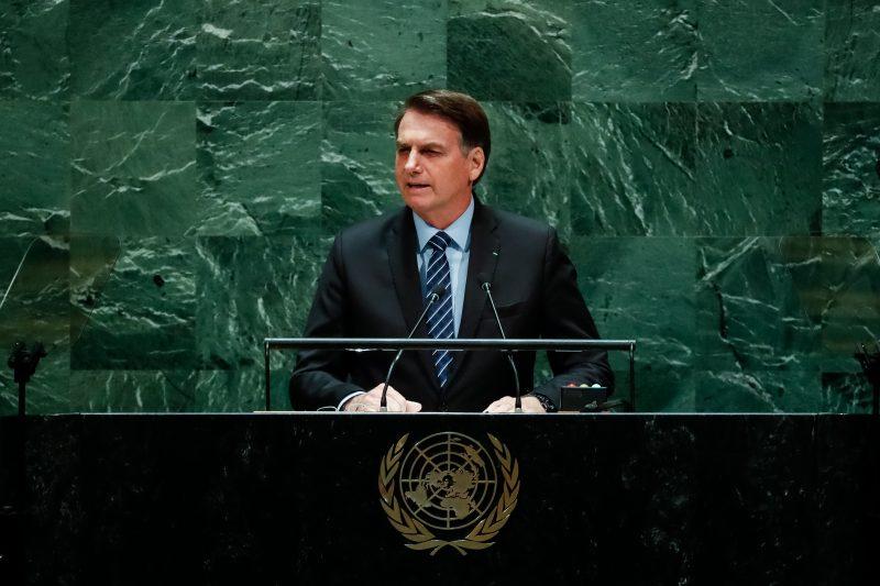 Presidente Bolsonaro discursando e usando terno preto e o fundo com piso verde escuro e na frente é possível ver o o símbolo da ONU