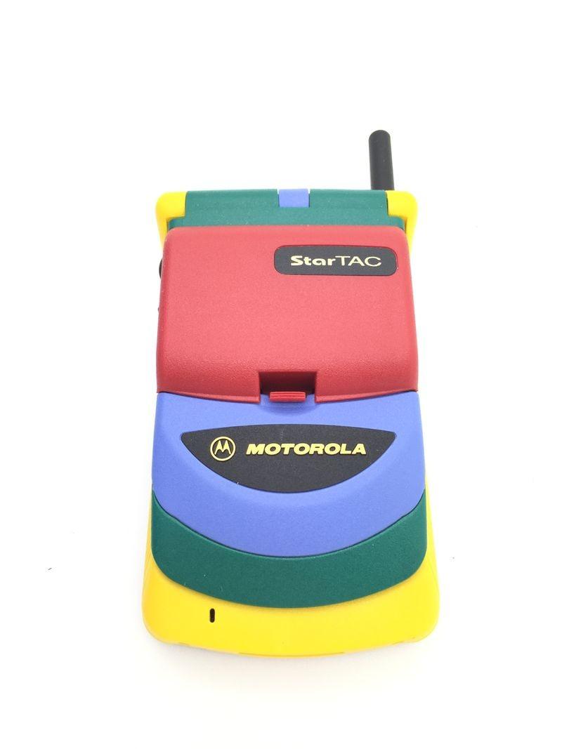 """Celulares fora do padrão: Motorola StarTAC Rainbow (1997) – StarTAC foi um modelo flip que fez muito sucesso no final da década de 1990. Porém, o que não ganhou fama foi sua versão Rainbow. Colorido, o celular parecia mais ter sido feito para o público infantil. Até porque lembrava algum brinquedo, como o gravador """"Meu Primeiro Gradiente"""". - Crédito: Divulgação/33Giga/ND"""