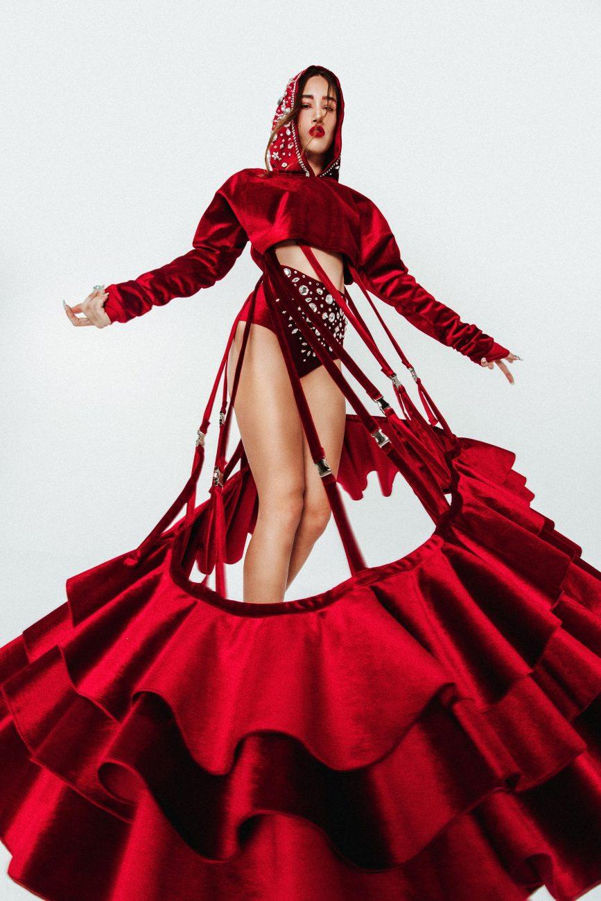 Augurio, por Tainá Bernard. Augurio viaja até a Espanha para buscar inspiração no Flamenco urbano, estilo propagado pela cantora Rosalía. O Flamenco é uma cultura antiguíssima, passada oralmente de geração em geração. É um ritmo que mistura o latino com o oriental, com vozes que choram enquanto cantam adiante seus sofrimentos. A dança é de movimentos bruscos e ao mesmo tempo delicados, sempre com muita emoção. Atualizar essa cultura é um assunto bastante controverso, mas também não se pode negar que é como se mantém algo vivo: transformando, adaptando. A coleção busca manter as origens do flamenco e as suas saias clavel misturando- as com parcas, moletons, camisetas e tênis. Essa dualidade entre o antigo e o novo também se vê na mistura inusitada de tecidos luxuosos utilizados em modelagens urbanas. As muitas joias utilizadas na cultura cigana vem representadas através das aplicações de pedrarias. - Tainá Bernard/Divulgação