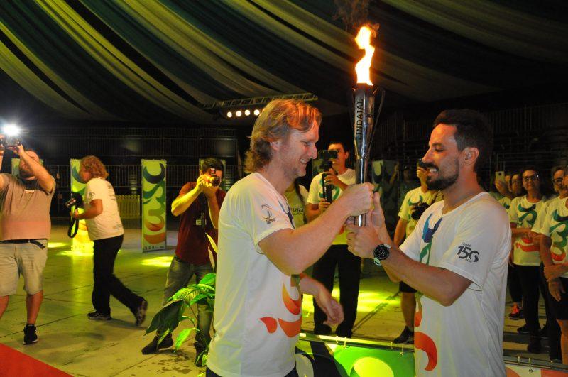 Prefeito de Timbó, Jorge Kruger, entrega a tocha para Paulo Müller, representando o pai John Müller – Foto: Orlando Pereira/ND
