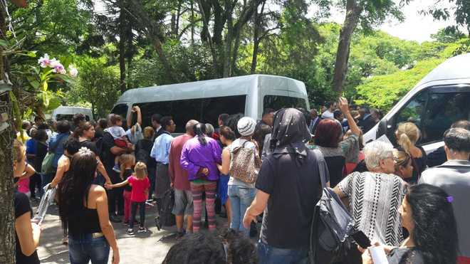 A van que levaria a família de Gugu deixou o cemitério sob aplausos dos fãs - Joyce Ribeiro/R7