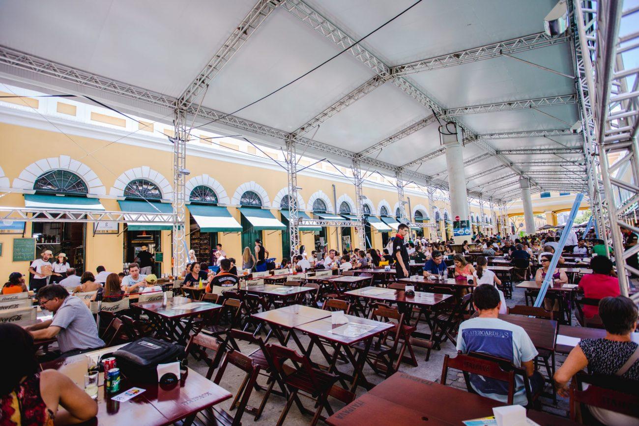 """3. Mercado Público de FlorianópolisO Mercado Público de Florianópolis reúne o melhor da gastronomia de Florianópolis além de boas opções de cervejas. Os tradicionais restaurantes — Box 32, Balção Mané e Boteco VaiQuemQuer — servem pratos fartos onde peixe, camarão, ostras e marisco são as estrelas.Com mesas distribuídas em seu vão central o Mercado Público de Florianópolis fica aberto de domingo à domingo. Além de comida boa, o público pode desfrutar de diversos rótulos de cerveja artesanais, muitas produzidas aqui mesmo.O som também é garantido com show de música ao vivo. É possível ouvir sucessos de Bob Marley, Capital Inicial, Skank e até Nirvana. O couvert artístico é opcional.Também é possível adquirir lembranças da Ilha, como chaveiros, blusas e canecas com os dizeres manezinhos clássicos. """"Ó-lhó-lhó"""" e""""Tax tolo?"""" são algumas das estampas.Como chegar: Qualquer ônibus que tenha como destino final o Ticen (Terminal de Integração do Centro) O quê fazer: Comer pratos de fruto do mar e beber chopes e cervejas artesanais - Daniel Queiroz/ND"""