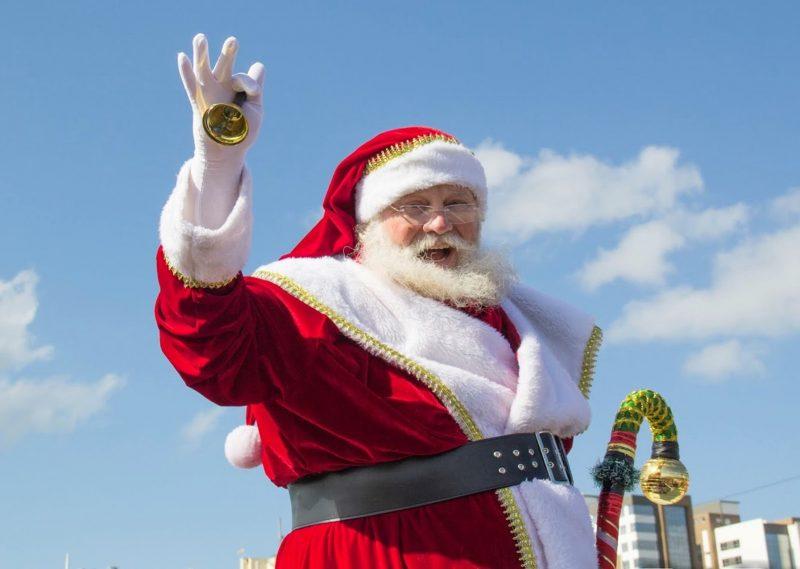 Papai Noel acena e sorri. Ele segura um sino e aparece o céu azul com poucas nuvens
