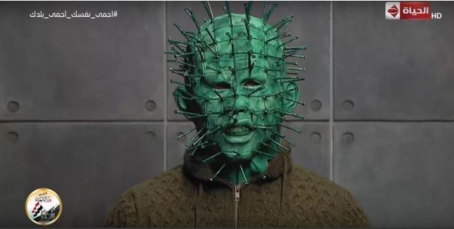 Em três minutos de puro conteúdo nonsense transmitido no último dia 9, Jaber troca uma ideia com alguém com máscara verde e cheio de pregos - Reprodução/YouTube/AlHayah TV Network