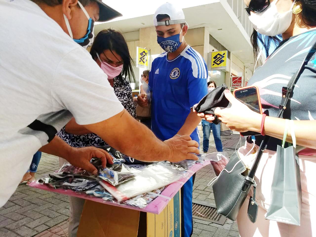 Paulo e a família atendem cliente nas ruas de Florianópolis. Eles vendem máscaras personalizadas com o símbolo de equipes de futebol - Ian Sell/ND