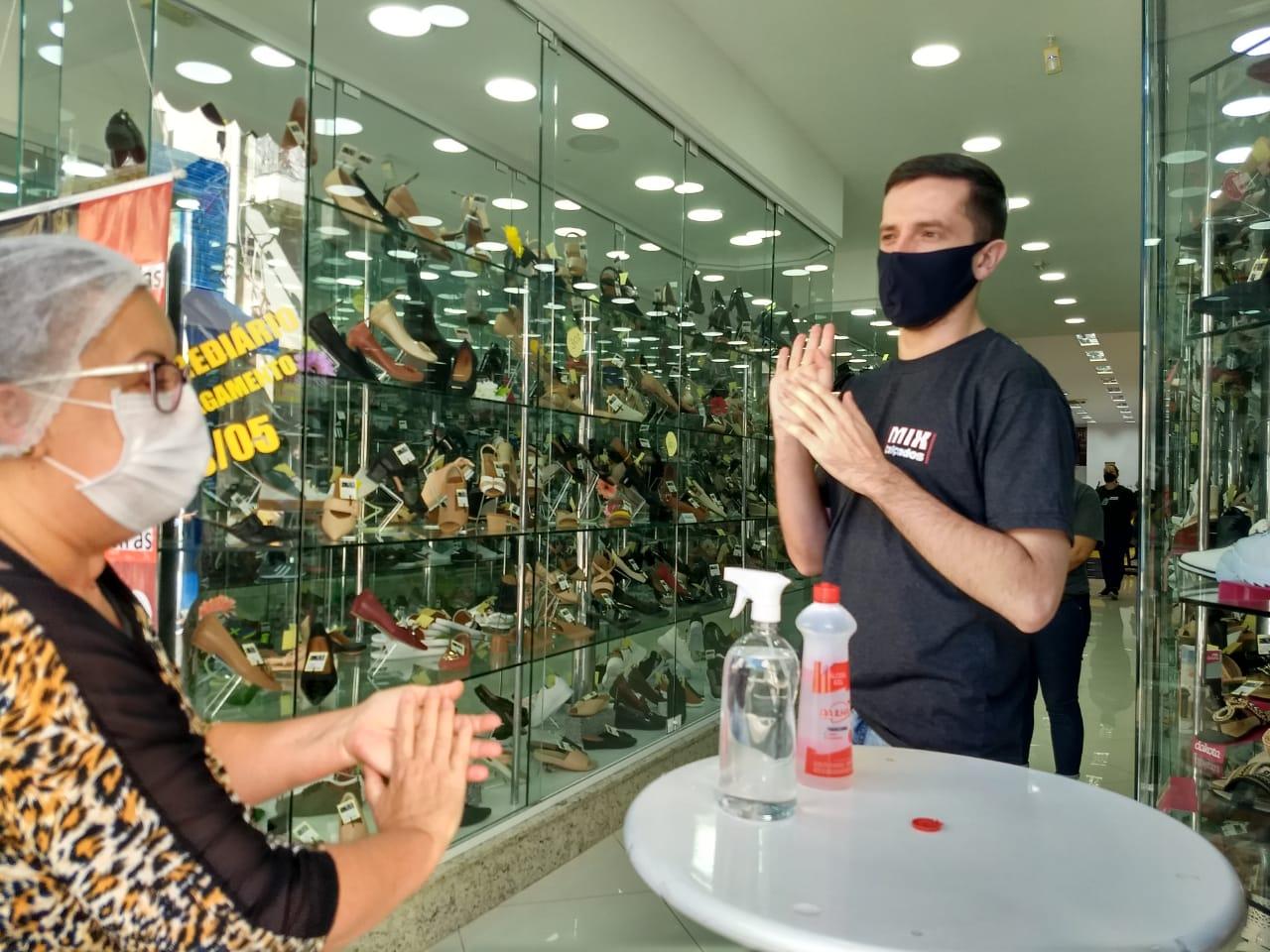 Vendedor instrui cliente na entrada da loja - Ian Sell/ND