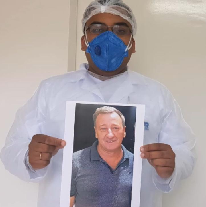 Ivor Demetrio Fossatti, de 56 anos, foi a primeira vítima de Covid-19 no Oeste catarinense. Morador de Tangará, ele foi diagnosticado com coronavírus no dia 1º de abril, após voltar de uma viagem ao litoral catarinense apresentando fortes sintomas da doença. Com o agravamento da infecção, ele foi internado em UTI, mas morreu no dia 18 de abril. Fossatti sofria de problemas cardíacos, que o levaram a fazer uma cirurgia no coração. Ele trabalhou por mais de 20 anos como Vigilante Sanitário na prefeitura de Tangará. Após a morte, colegas gravaram um vídeo em homenagem. Na imagem, um colega segura uma foto de Fossatti. Confira a reportagem completa: https://bit.ly/2yt0KZp - Reprodução/Facebook