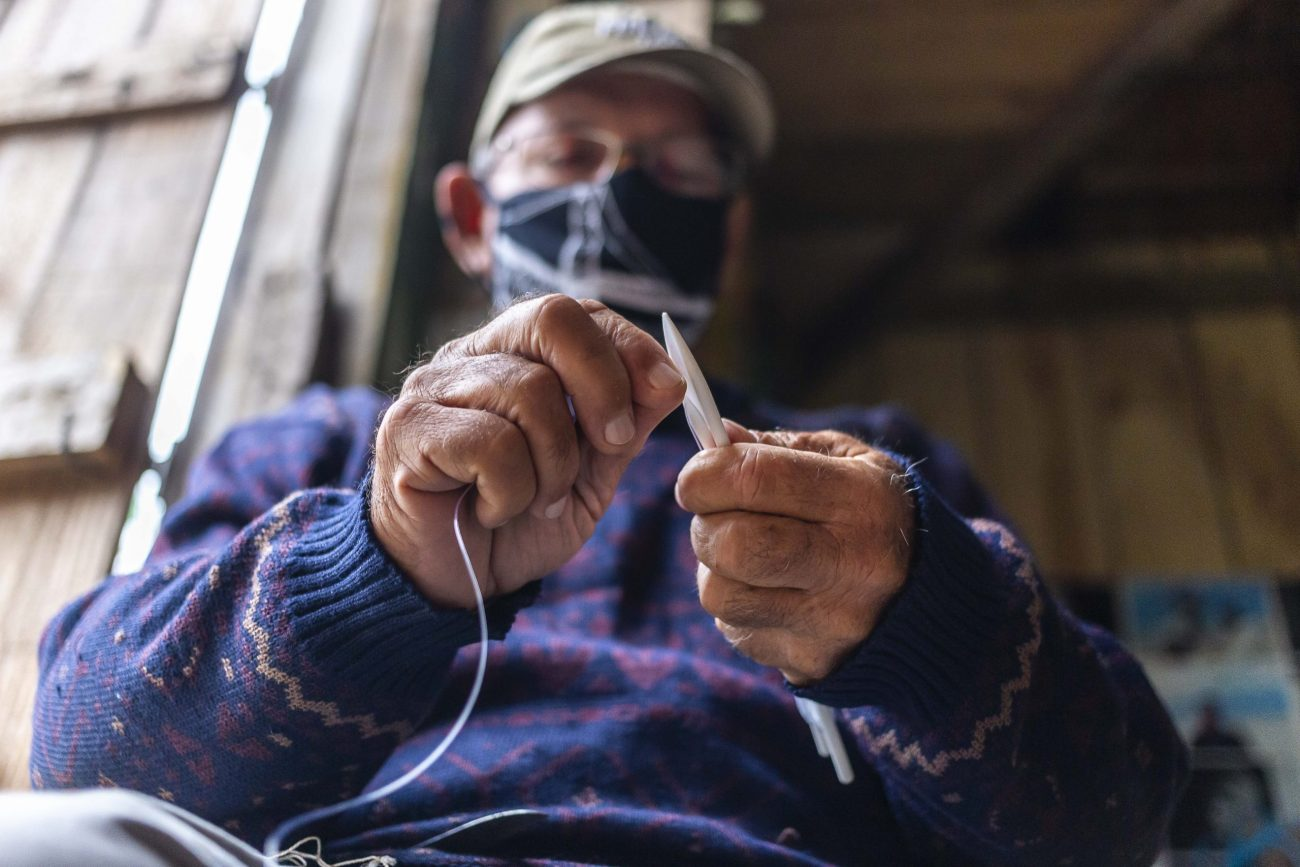 Nono Roupp ajuda os camaradas do Rancho FADA a remendar a rede de pesca - Anderson Coelho/ND