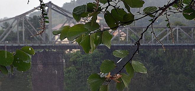 Imagem da Ponte de Ferro em segundo plano. Na imagem é possível observar que chove em Blumenau.