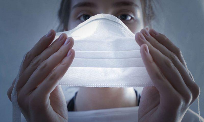 Na imagem aparece uma jovem com uma máscara branca das mãos cobrindo nariz e boca.