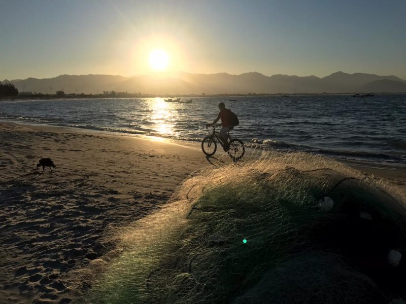 Imagem mostra céu de SC com sol e um homem andando de bicicleta na areia da praia