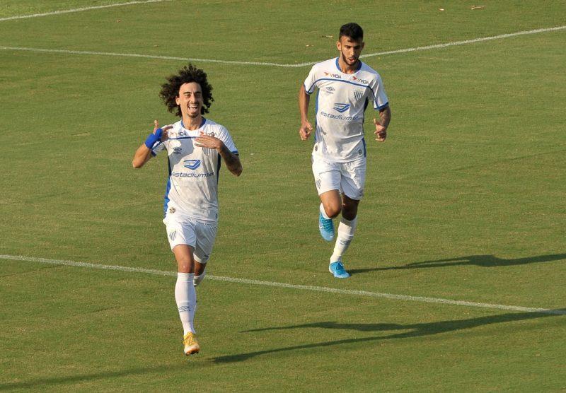 Valdívia está vestindo camisa branca do Avaí e comemorando gol pelo Avaí. Ao lado, aparece Lourenço correndo