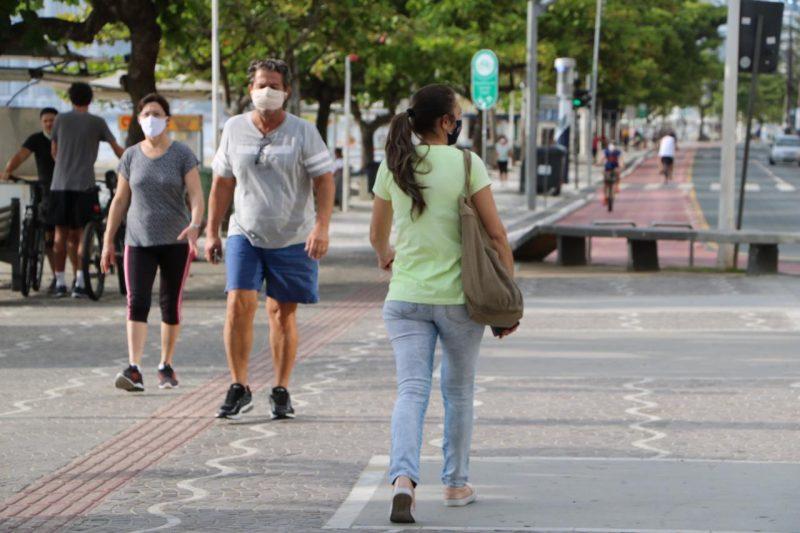 Pessoas caminhando na calçada de máscara