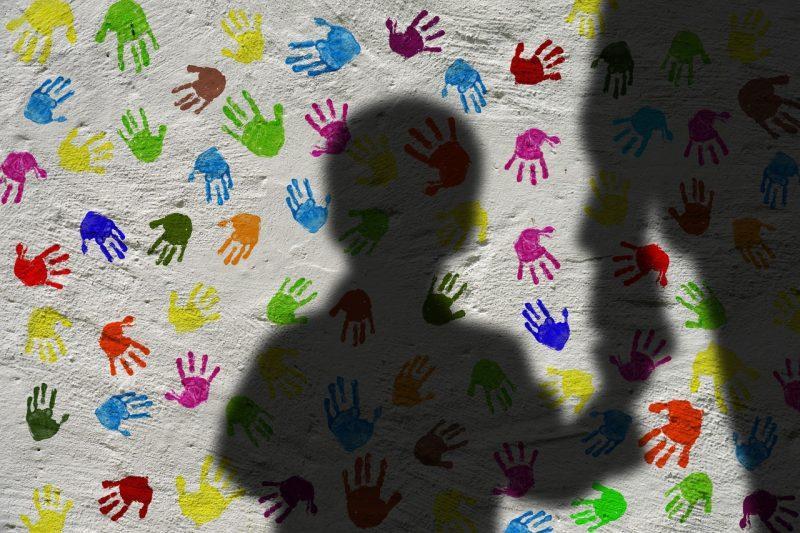 Imagem da sombra de uma criança de mãos dadas com um adulto. Ao fundo uma parede braca com várias marcas de mãos de crianças coloridas