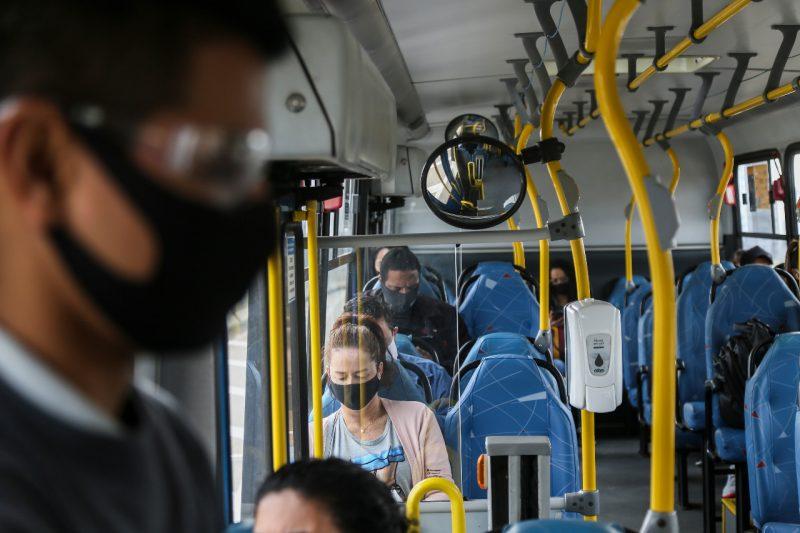 Pessoas dentro de ônibus e usando máscaras