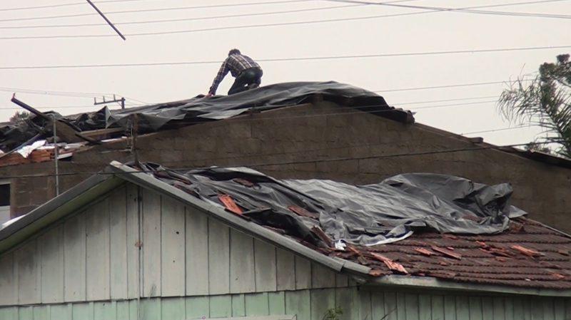 Moradores sobem aos telhados para amenizar os prejuízos do fenômeno – Foto: Carlos Corrêa/Reprodução NDTV