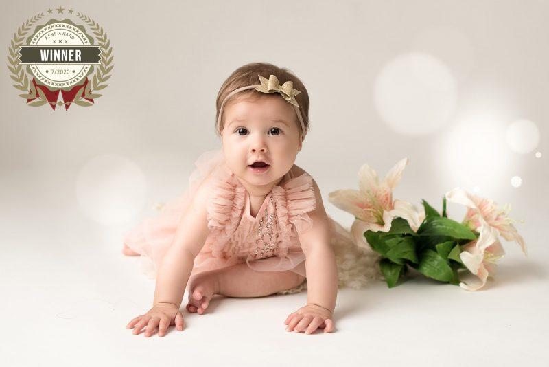 """A fotógrafa joinvilense Andreia Schroeder Isleb teve, recentemente, duas fotos premiadas no AFNS AWARD, um concurso internacional de fotografia para recém-nascidos e maternidade. Na foto premiada acima, Lívia tinha 7 meses. Foi feita no acompanhamento desde que nasceu até 1 ano de idade. Uma bebê linda, derrete-se Andreia. Segundo a fotógrafa, todas as sessões foram uma alegria. """"Eu queria transmitir esse brilho, delicadeza e graça que ela transmite para a gente, junto com as cores neutras e delicadas"""", conclui. – Foto: Andreia Isleb/ND"""