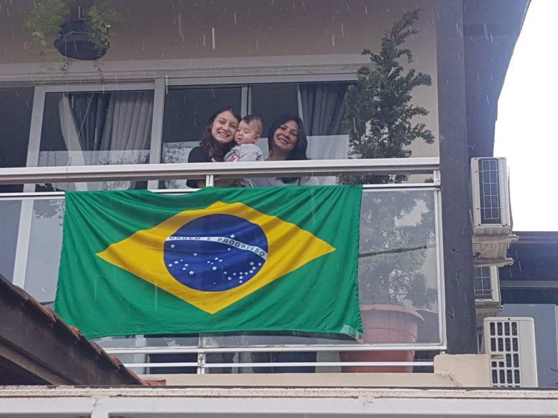 Daniela, Maria Eduarda e o pequeno Pedro exibem a bandeira brasileira na sacada, no bairro Ingleses – Foto: Reprodução/Arquivo pessoal