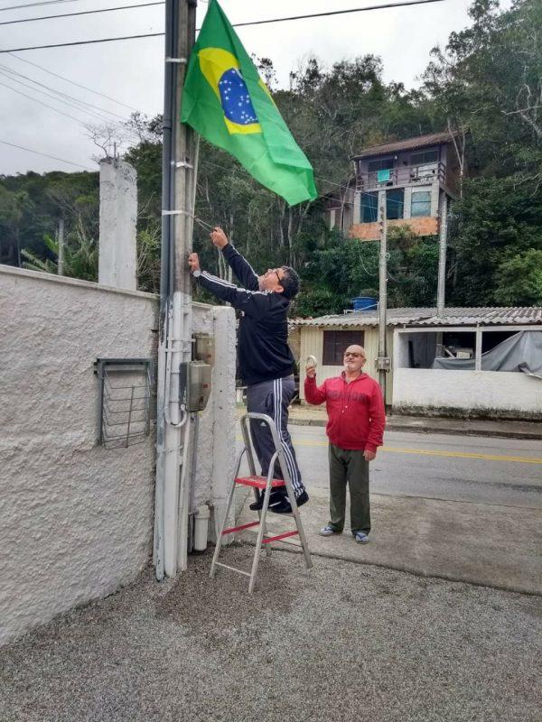 Edenir e Odevaldo hastearam a bandeira na Praia do Antenor, em Governador Celso Ramos – Foto: Reprodução/Arquivo pessoal