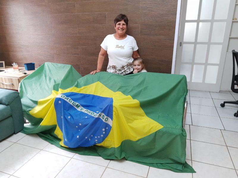 Landa e a neta Julia com a bandeira nacional. no bairro Carianos. – Foto: Reprodução/Arquivo pessoal