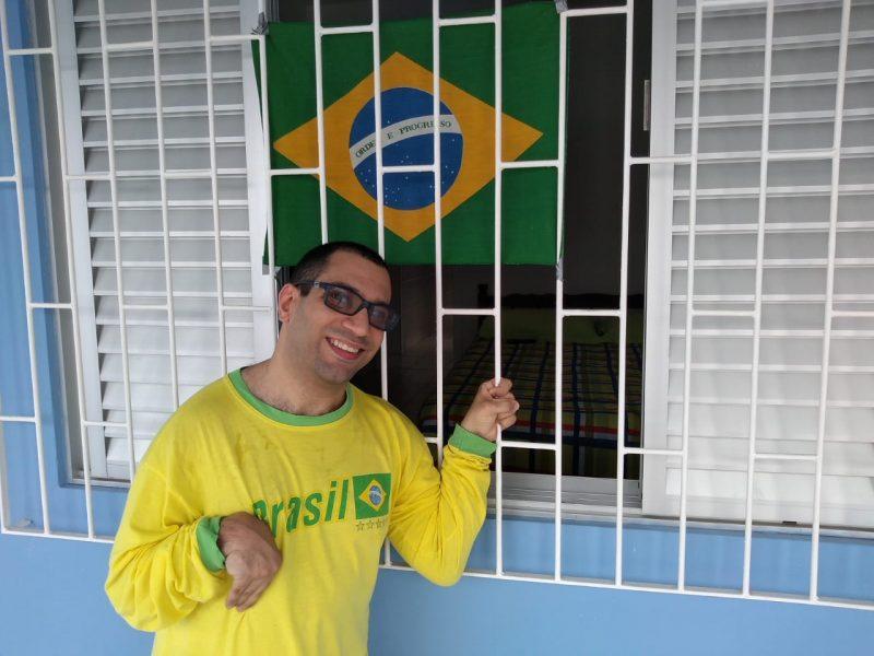 Lucas, de Palhoça, exibe o verde e amarelo junto à bandeira do Brasil – Foto: Reprodução/Arquivo pessoal/Lucas Silvy