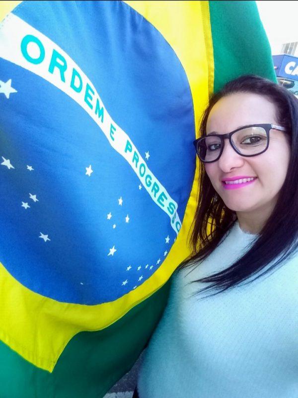 Marcela, de Navegantes, celebrando ao lado da bandeira do Brasil. – Foto: Arquivo pessoal/Marcela Inês Gervásio Cavalli