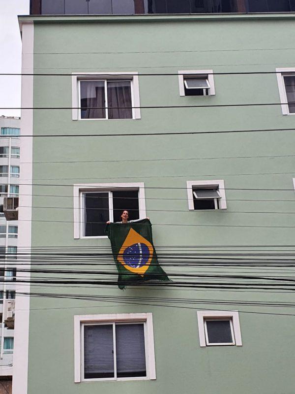 Moradora de Balneário Camboriú estendeu a bandeira do Brasil na janela do apartamento para prestigiar a carreata que passou pelo Centro da cidade. – Foto: Marcelo Nunes/NDTV Record