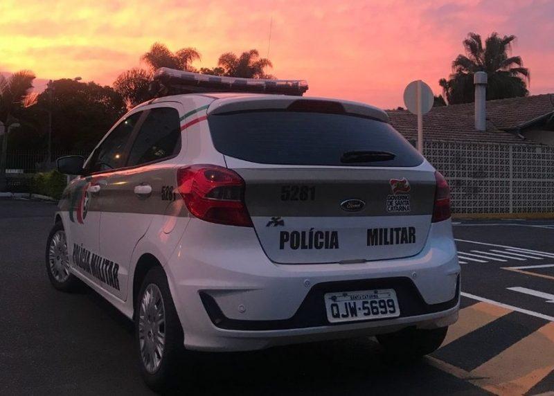 Foto de uma viatura da Polícia Militar parada às margens de uma rua com um cenário de pôr do sol.
