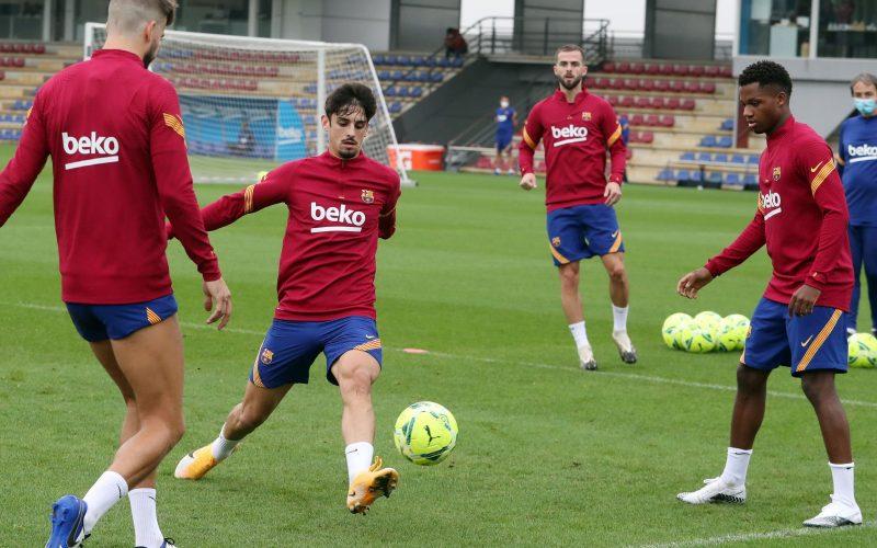 Jogadores do Barcelona tocam a bola em campo de treinamento